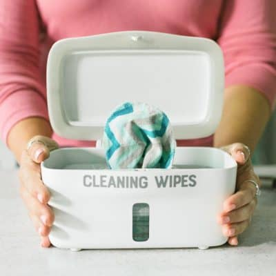 Woman's hands holding a wipes dispenser full of DIY Disinfecting Wipes.
