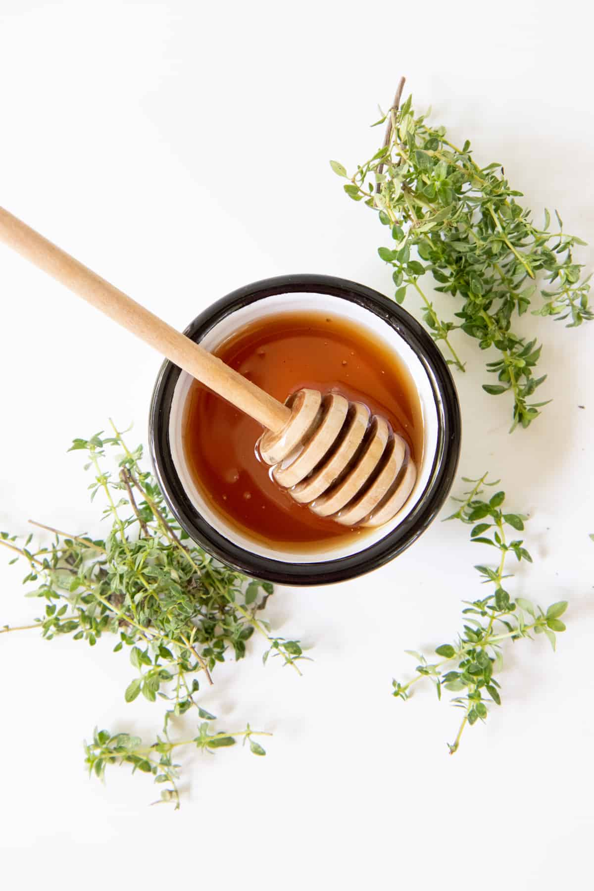 Honey in a small dish with a honey dipper. The dish is surrounded by fresh lemon thyme.