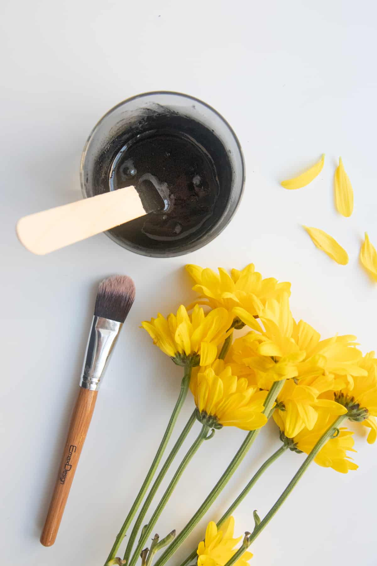 Jar of activated charcoal face mask next to yellow flowers.