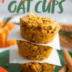 "Three Pumpkin Spice Baked Oatmeal Cups stacked on a green plate, with pieces of parchment paper separating them. A text overlay reads ""Baked Meal Prep Pumpkin Spice Oat Cups."""