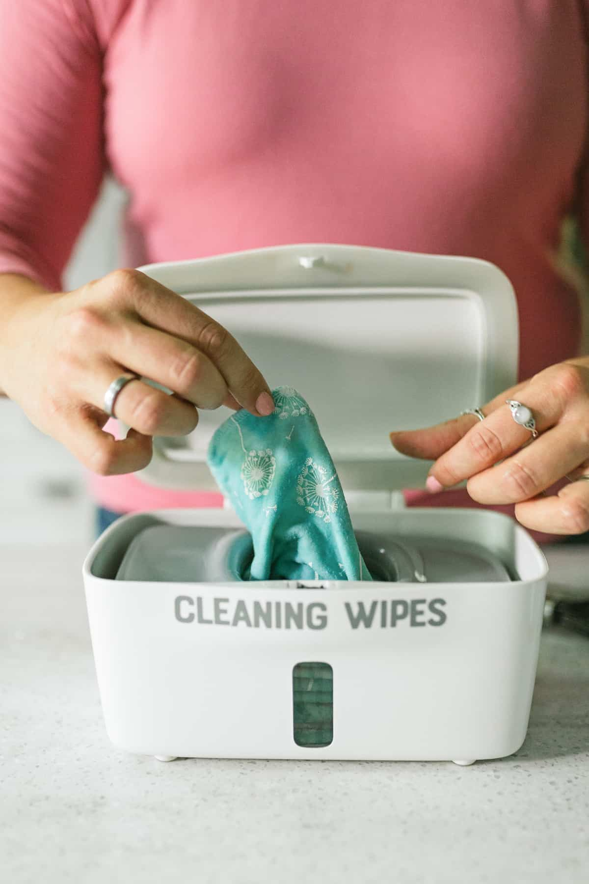 Woman's hands pulling DIY Disinfecting Wipes out of a dispenser.