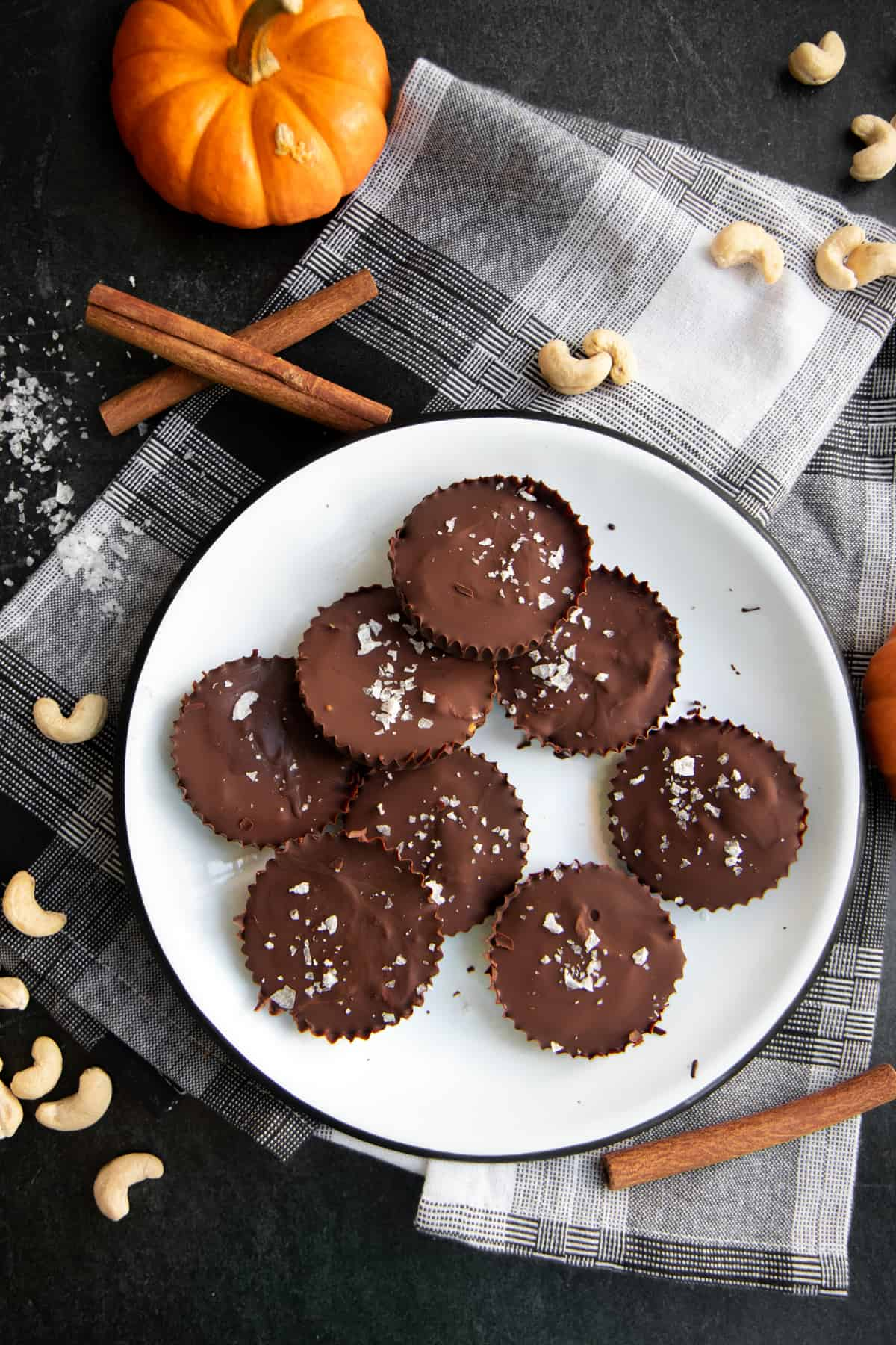 Pumpkin Spice Dark Chocolate Nut Butter Cups arranged on a white plate on top of a plaid background.