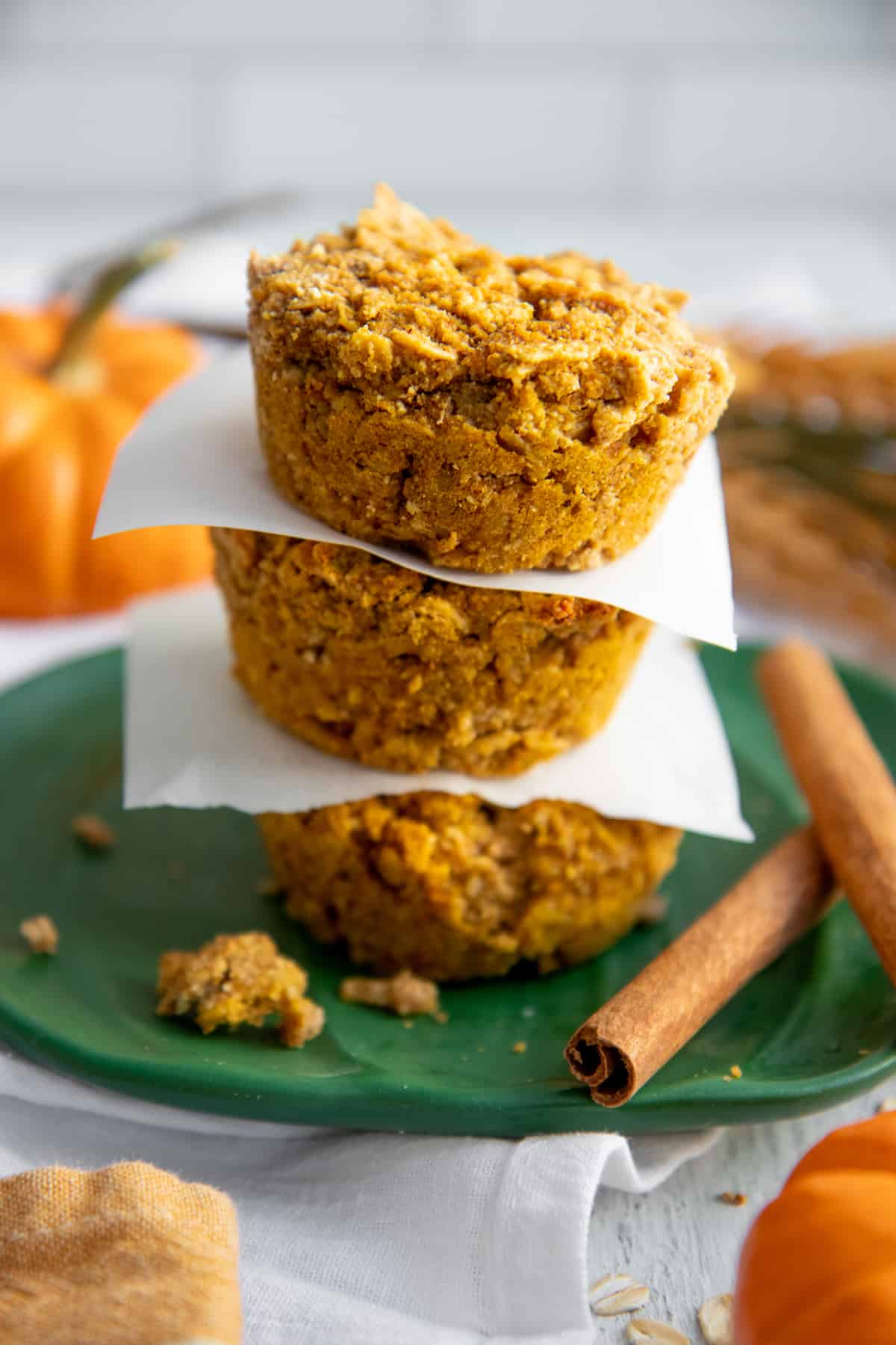Three Pumpkin Spice Baked Oatmeal Cups stacked on a green plate, with pieces of parchment paper separating them