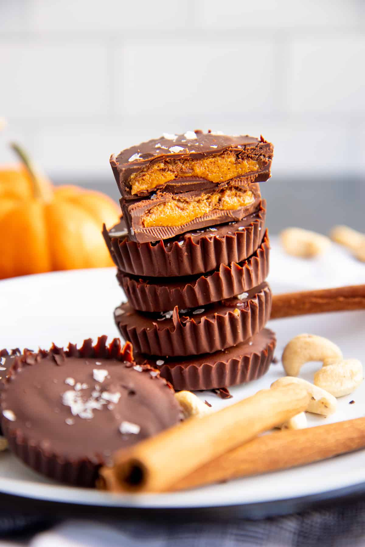 Stack of Pumpkin Spice Dark Chocolate Nut Butter Cups arranged on a white plate. One of the cups is cut in half to show the filling.