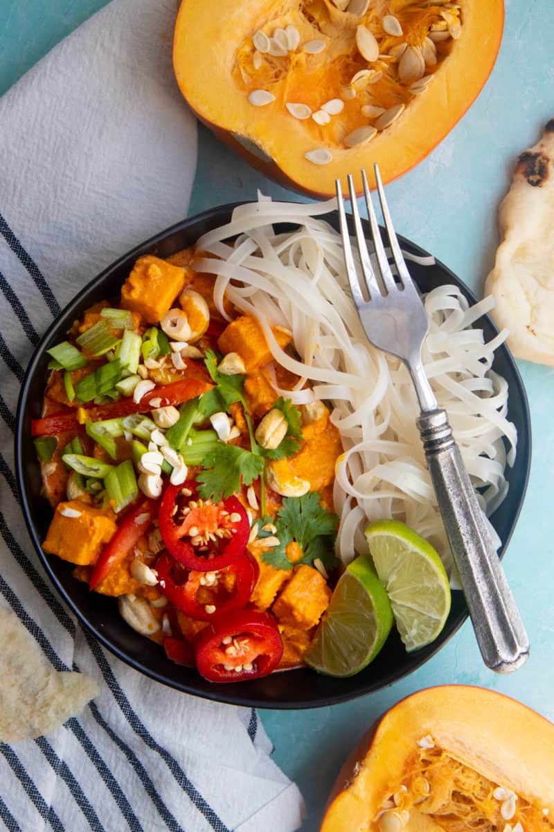 Vegan one pot pumpkin curry served over a bed of rice noodles, in a black dish on a light blue table.