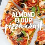 "Baked veggie pizza sliced and sitting on parchment paper. A text overlay reads ""Almond Flour Pizza Crust."""