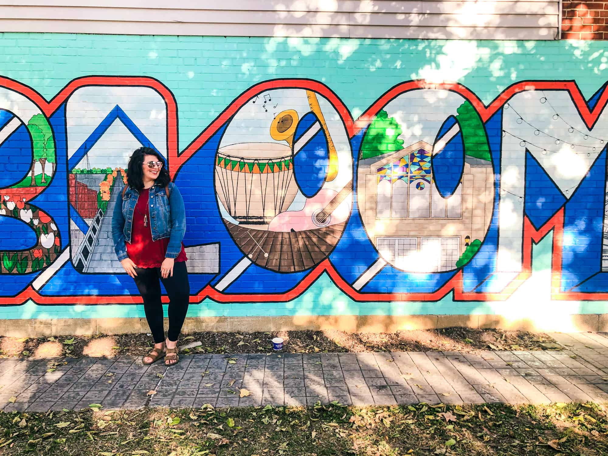 """Brunette woman in leggings and a denim jacket stands in front of a painted mural that says """"Bloomington,"""" though only the """"Bloom"""" is visible."""