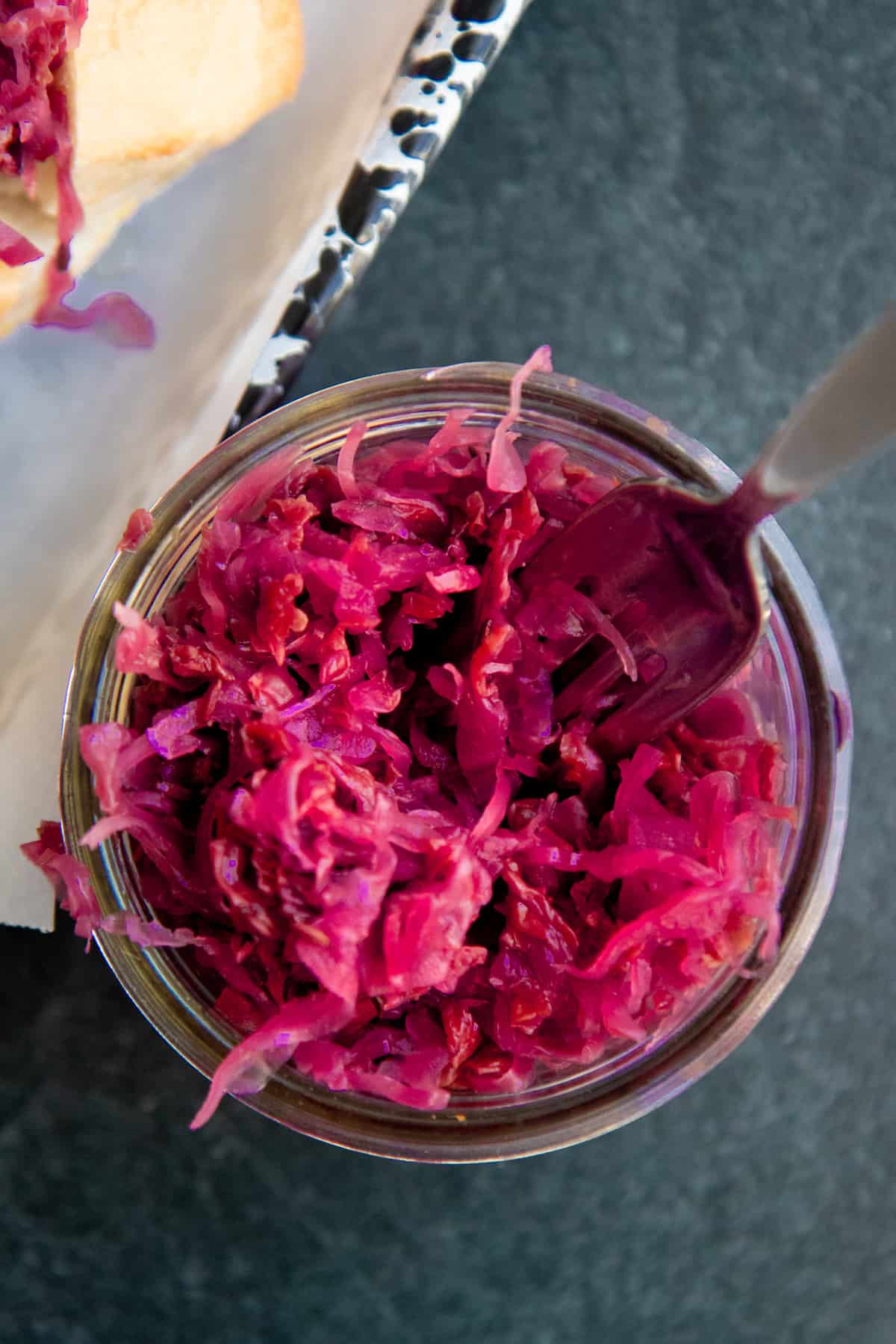 A fork dips into a glass jar of homemade sauerkraut.
