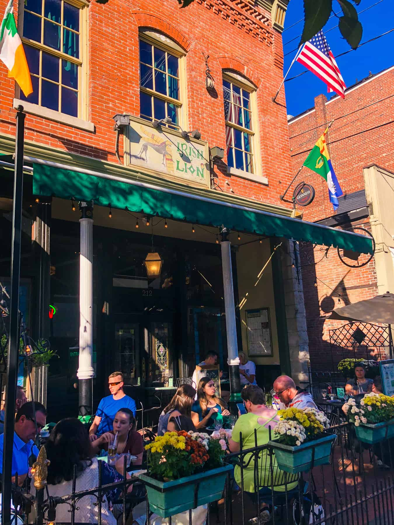 The outside of the Irish Lion in Bloomington, IN. The restaurant is in a brick building with a green awning.