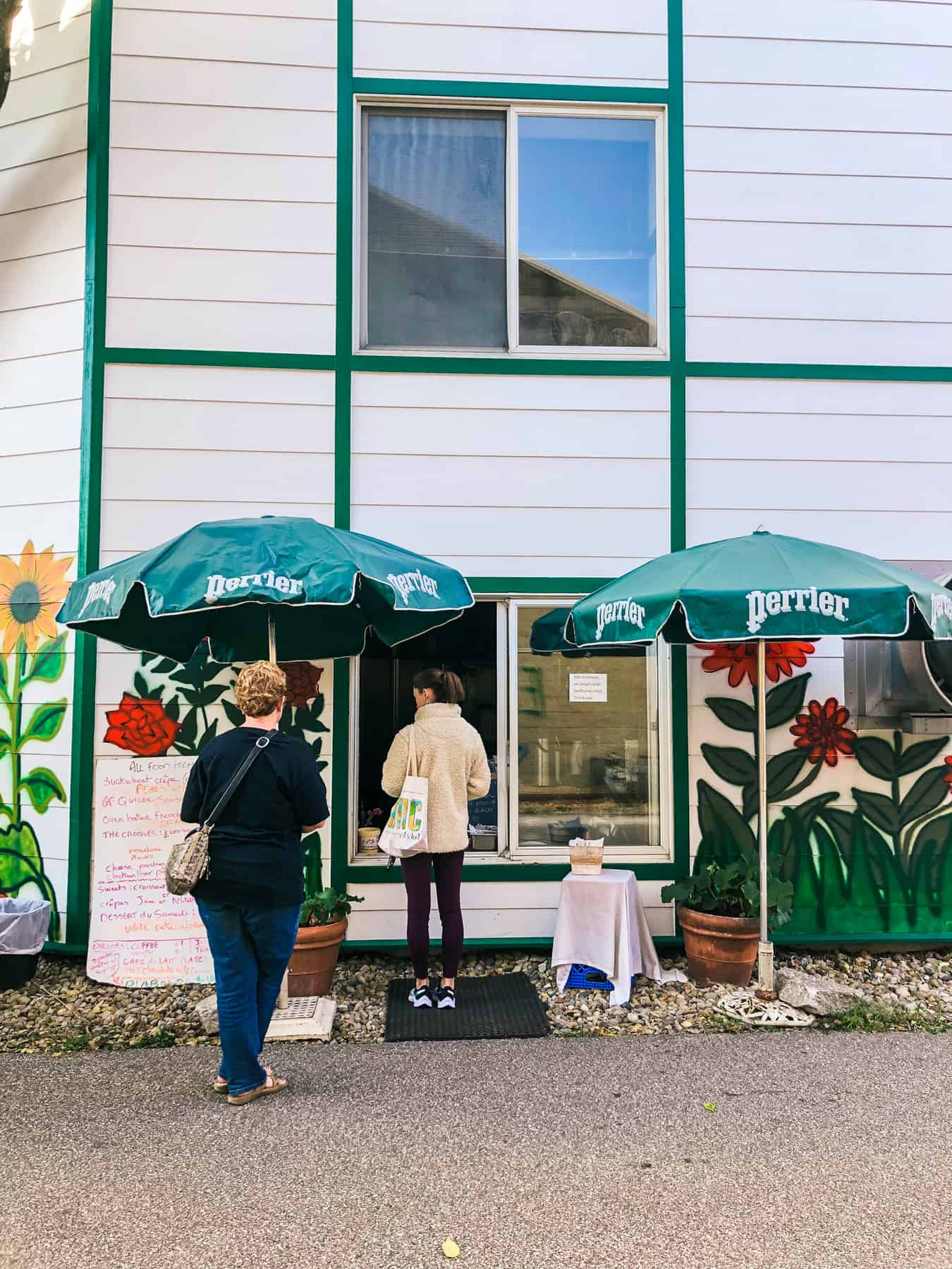 People walk up to order at the window of a building with white siding and green trim. Green patio umbrellas sit outside next to a white board with a menu for Le Petit Cafe.
