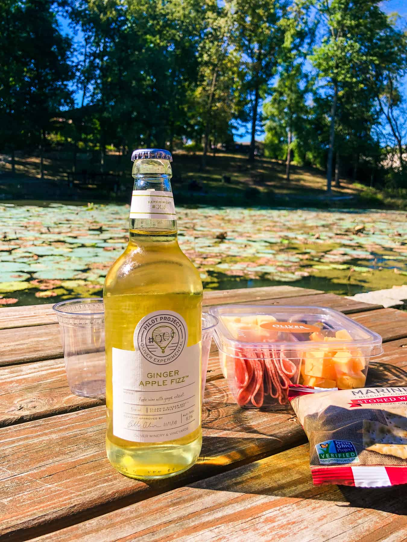 A clear bottle of Ginger Apple Fizz from Oliver Winery sits on a picnic table in front of a pond covered in lily pads.