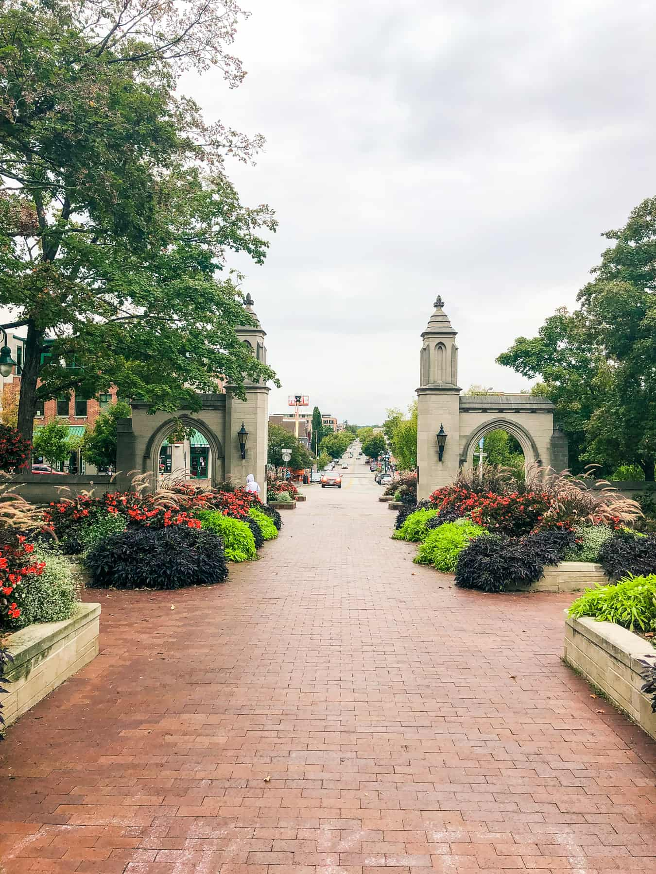 Outside views of Indiana University. A wide brick walkway is bordered by flower beds.