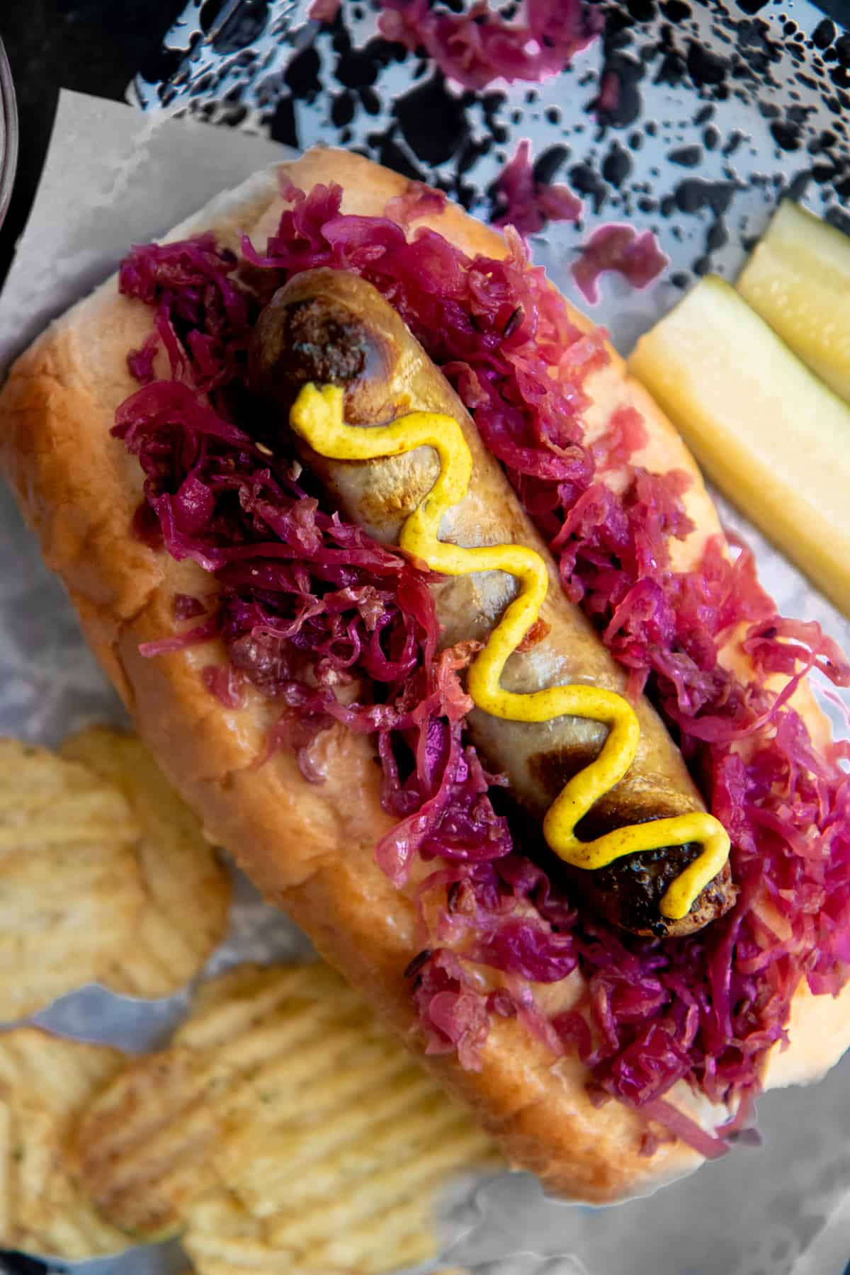 A brat drizzled with mustard sits on a bed of red sauerkraut on top of a bun. Potato chips and a sliced pickle surround the brat.