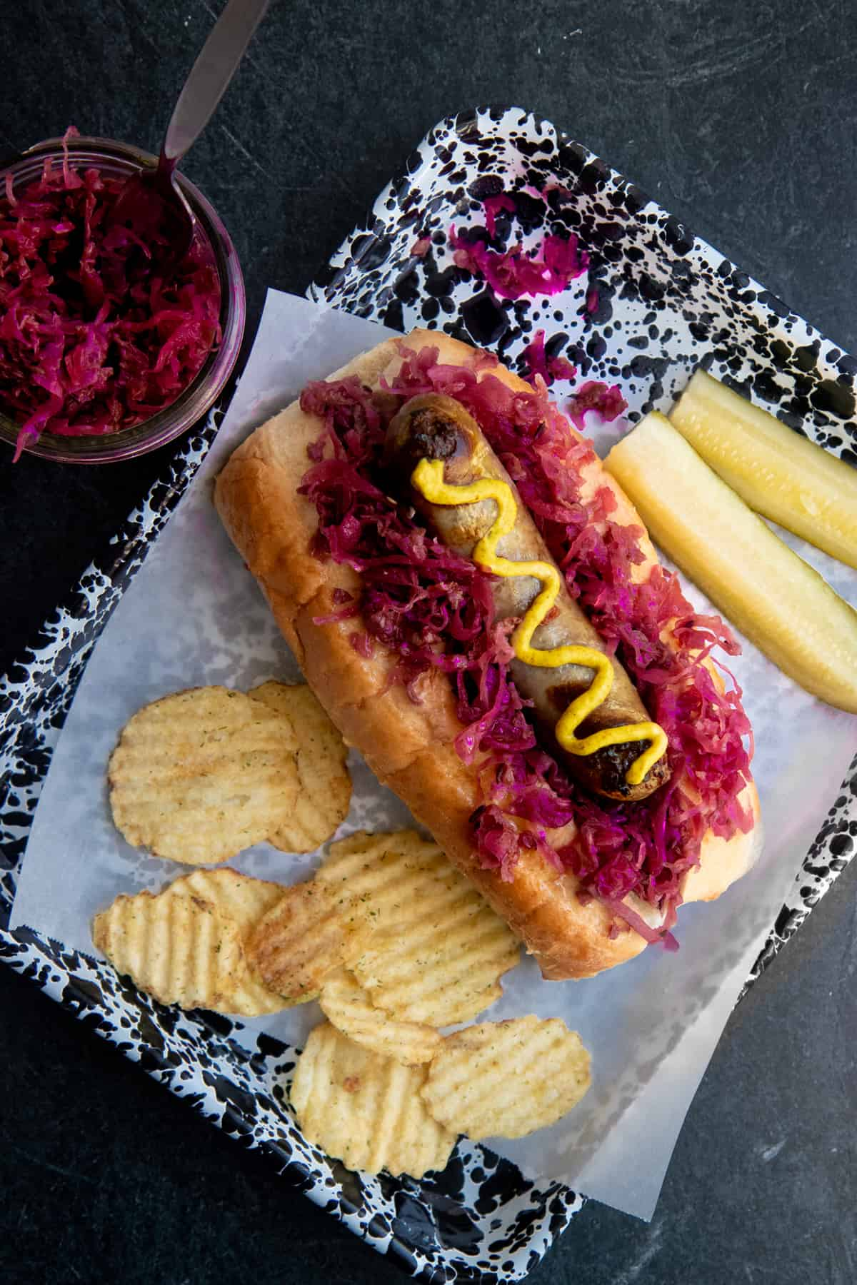 A brat drizzled with mustard sits on a bed of homemade sauerkraut on top of a bun. Potato chips and a sliced pickle surround the brat.