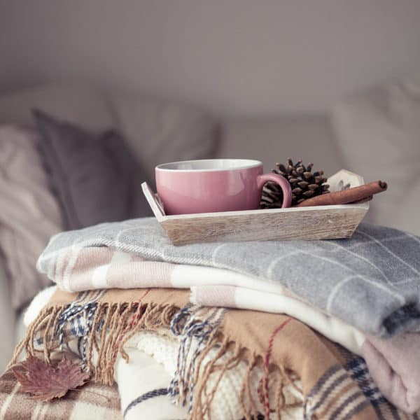 Stack of blankets topped with a tray holding a pink mug, a pine cone, and a cinnamon stick