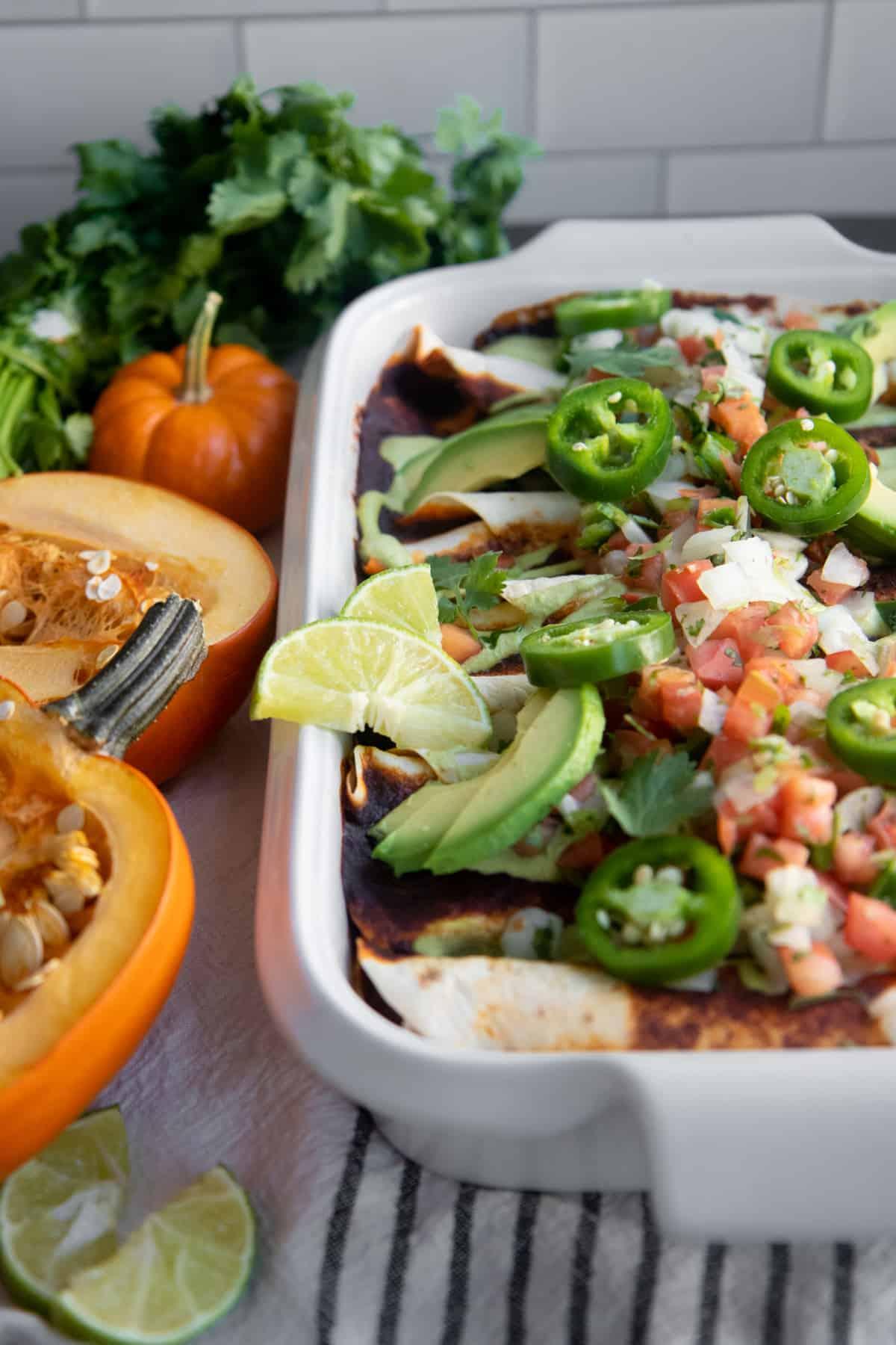 Pan of baked enchiladas next to a halved pumpkin.