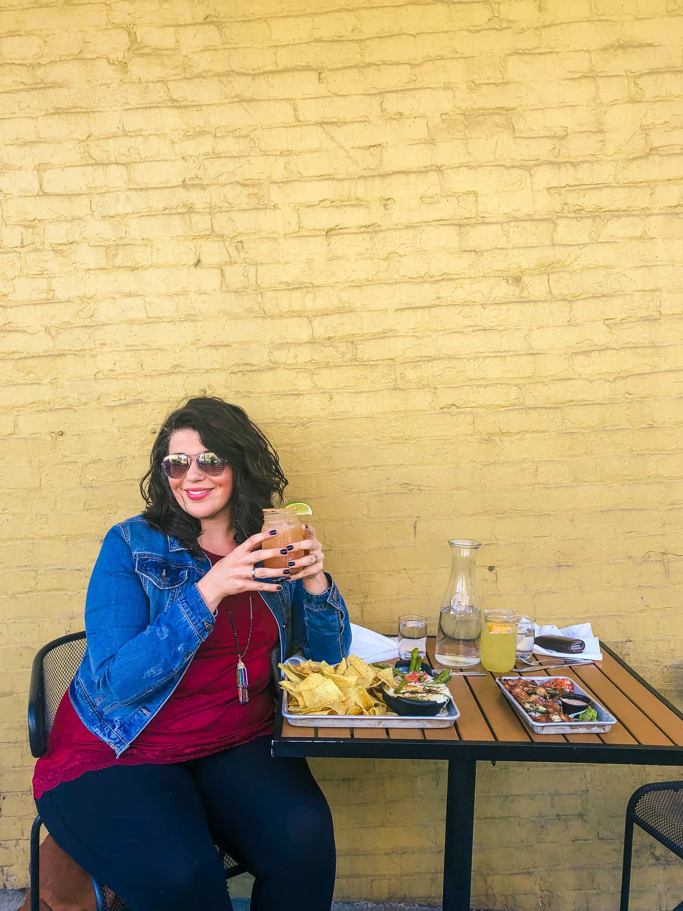 A brunette woman in sunglasses and a denim jacket sits eating outside next to a yellow brick wall.