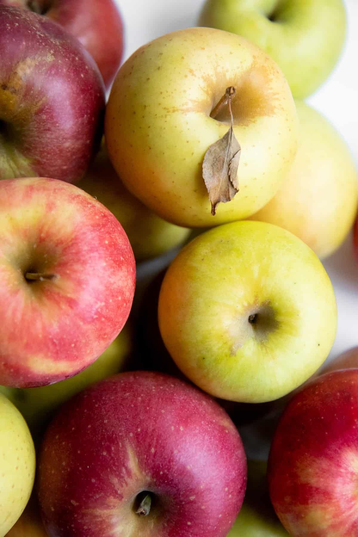 Close-up on a stack of yellow, green, and red apples.