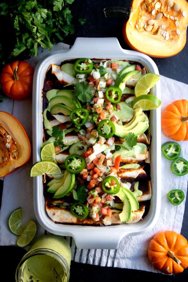 White casserole dish filled with Pumpkin and Black Bean Vegan Enchiladas