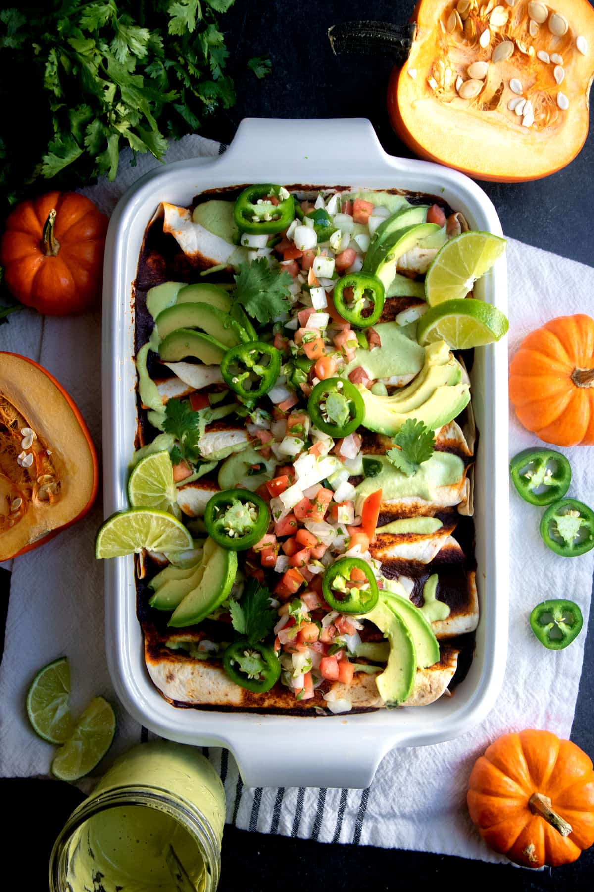 White casserole dish filled with Pumpkin and Black Bean Vegan Enchiladas