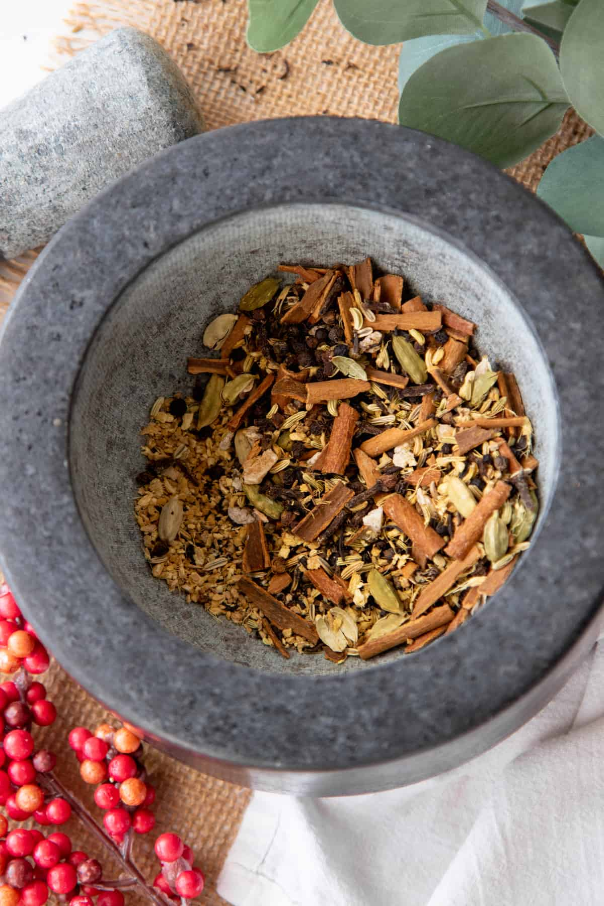 Crushed spices fill a gray mortar, after being crushed with a pestle.
