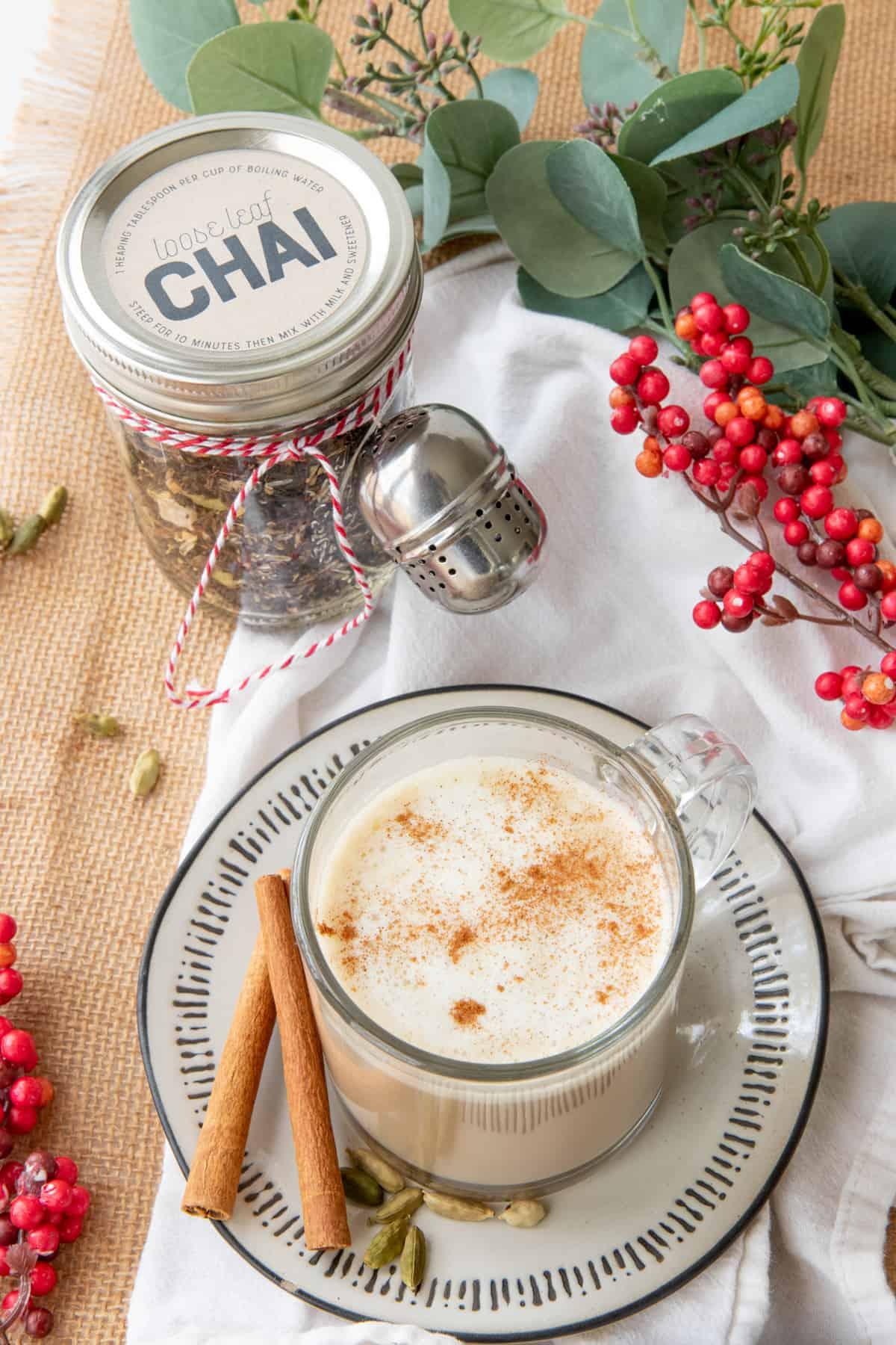 A glass mug filled with a chai latte sits next to a jar of loose leaf chai mix.