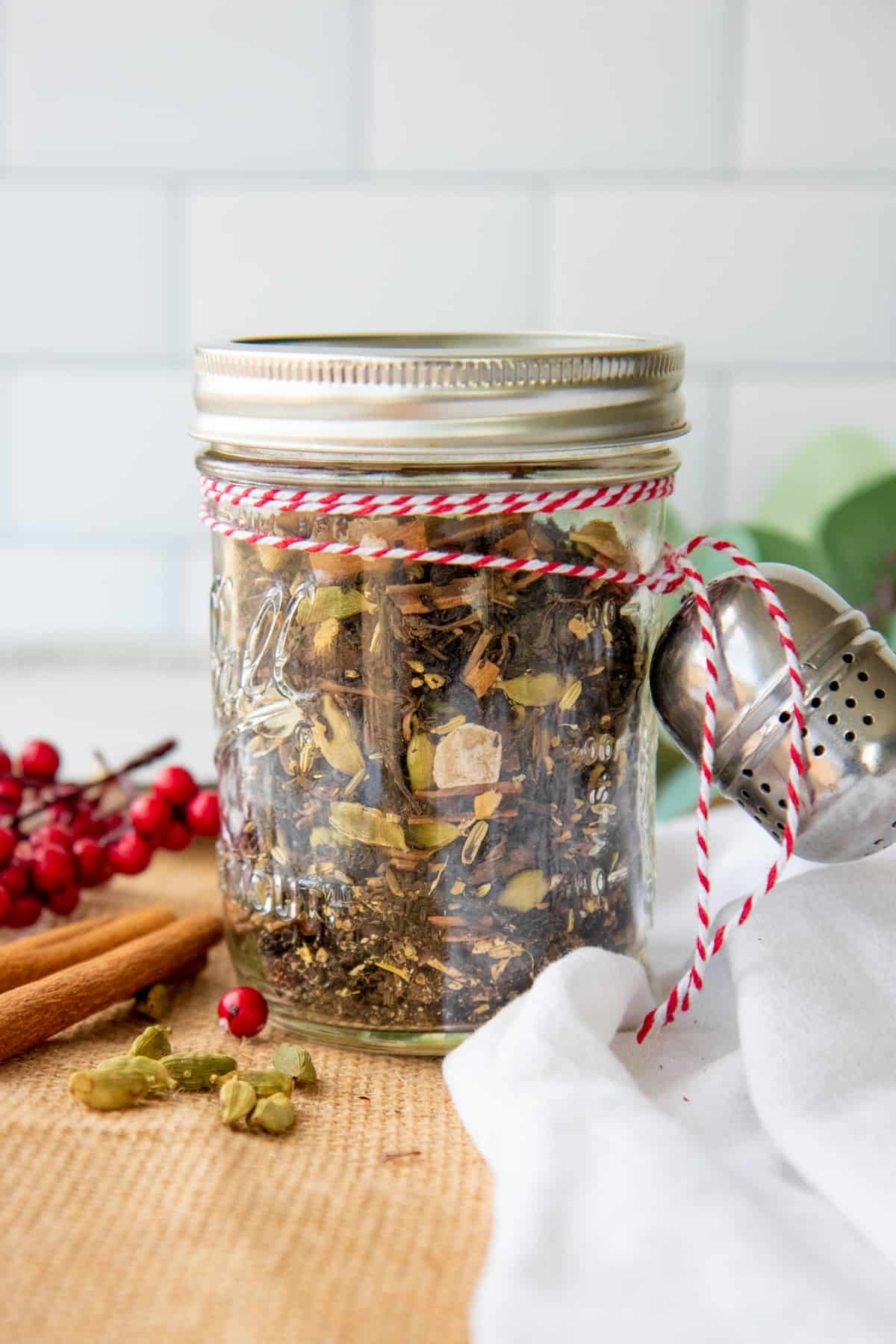 A glass jar filled with loose leaf is tied to a tea ball with baker's twine. The jar is surrounded by spices.