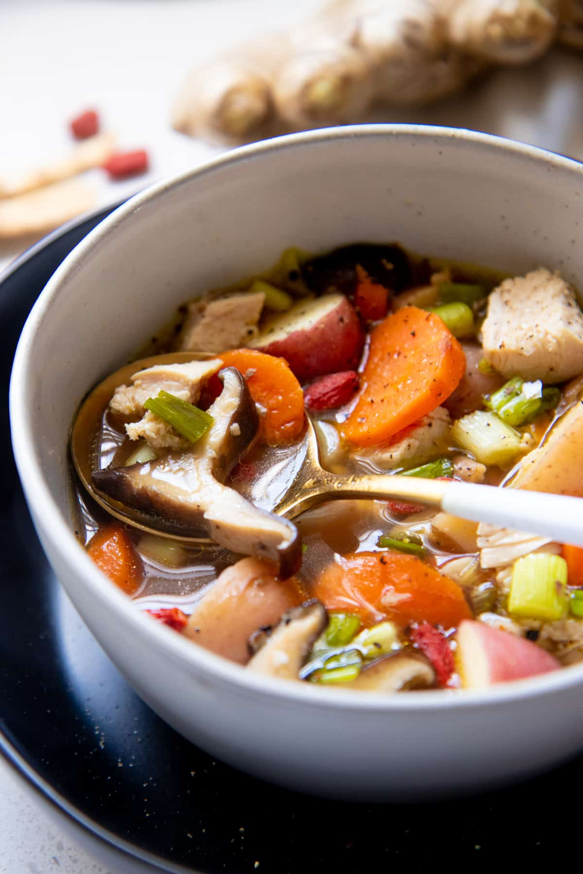 A spoon dips into a bowl full of soup broth, chicken, vegetables, and Chinese herbs.