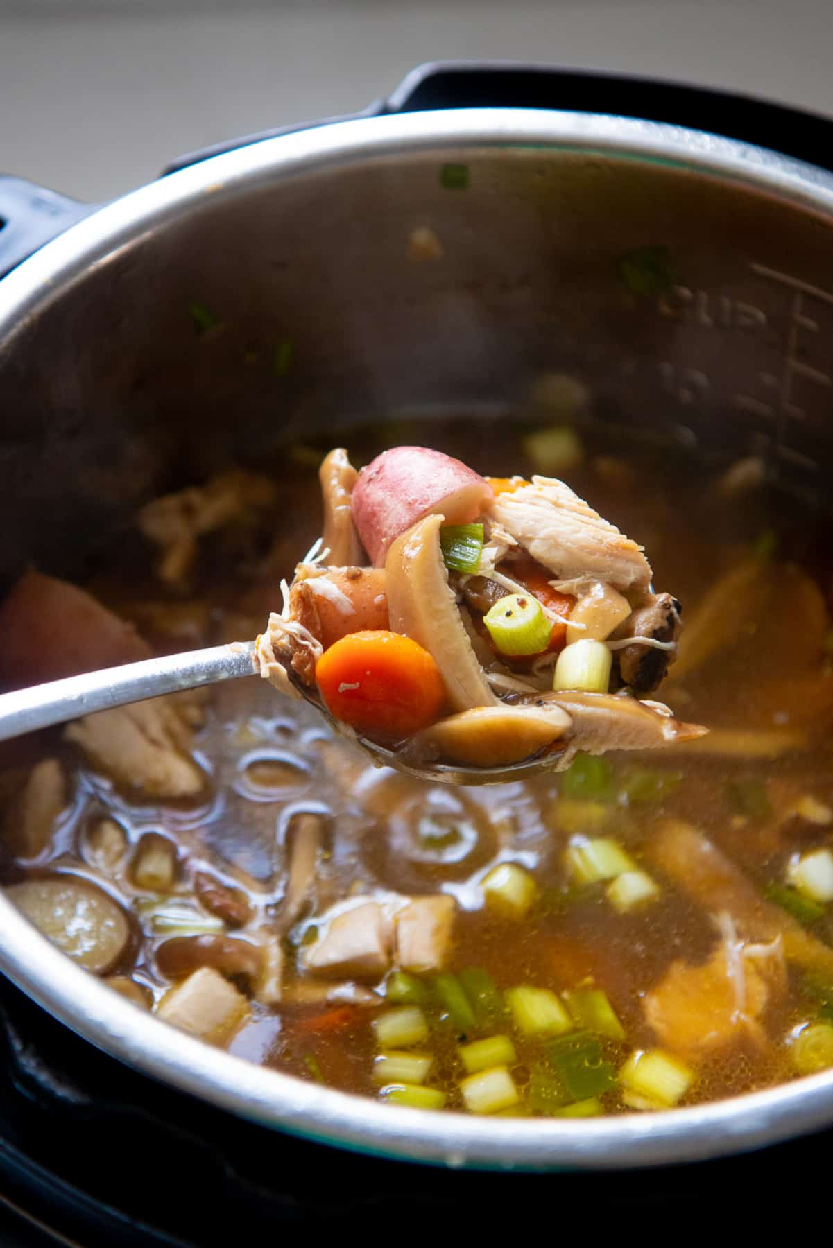 A spoon holds a scoop of soup over an open Instant Pot.