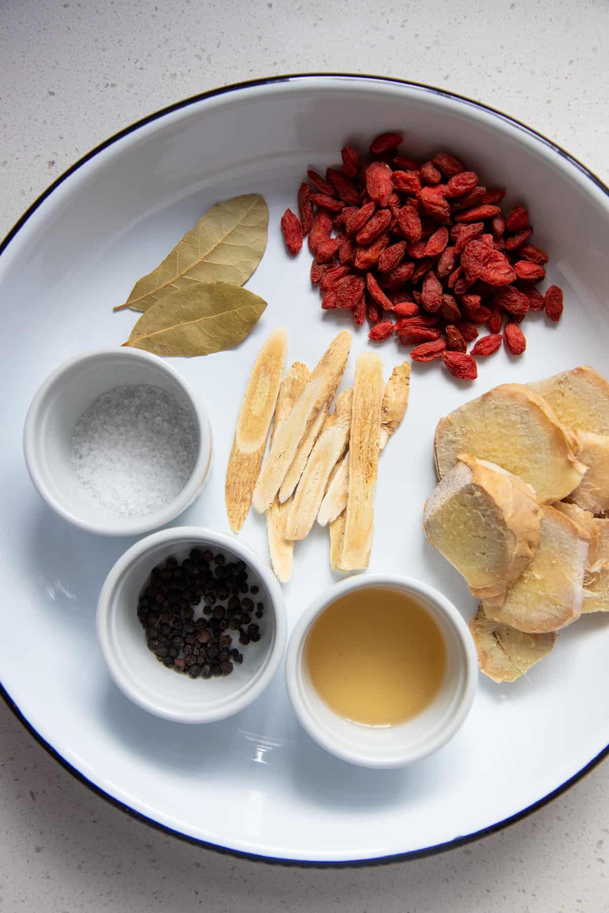 Ingredients are laid out on a white plate, including Chinese herbs and bay leaves.