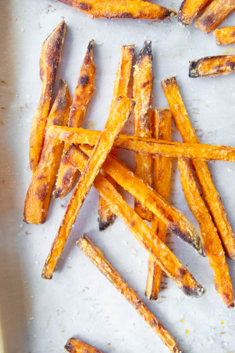 Sweet potato fries piled on top of each other on parchment paper.