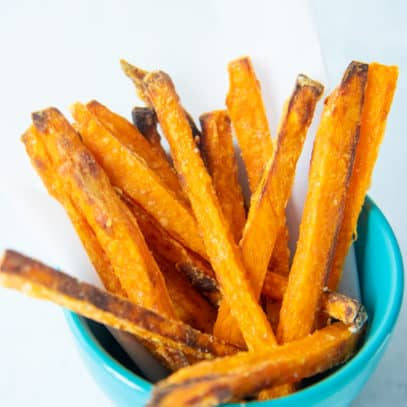 Close up of crispy baked sweet potato fries in a small blue bowl.