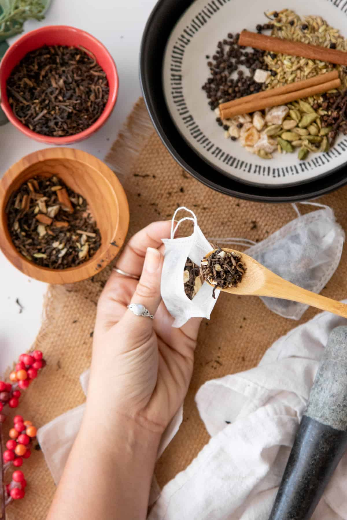 A wooden spoon scoops chai tea mix into fillable tea bags.