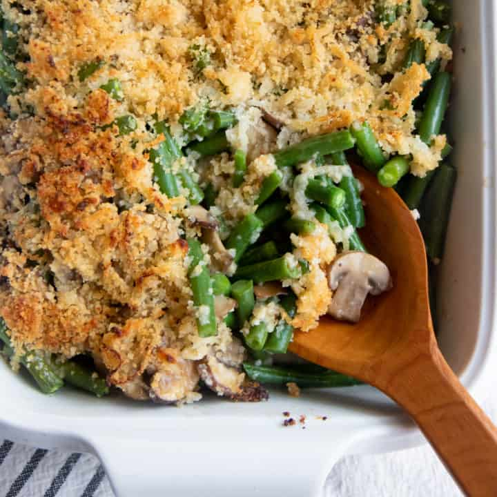 A wooden spoon scoops some fresh green bean casserole out of a white baking dish.