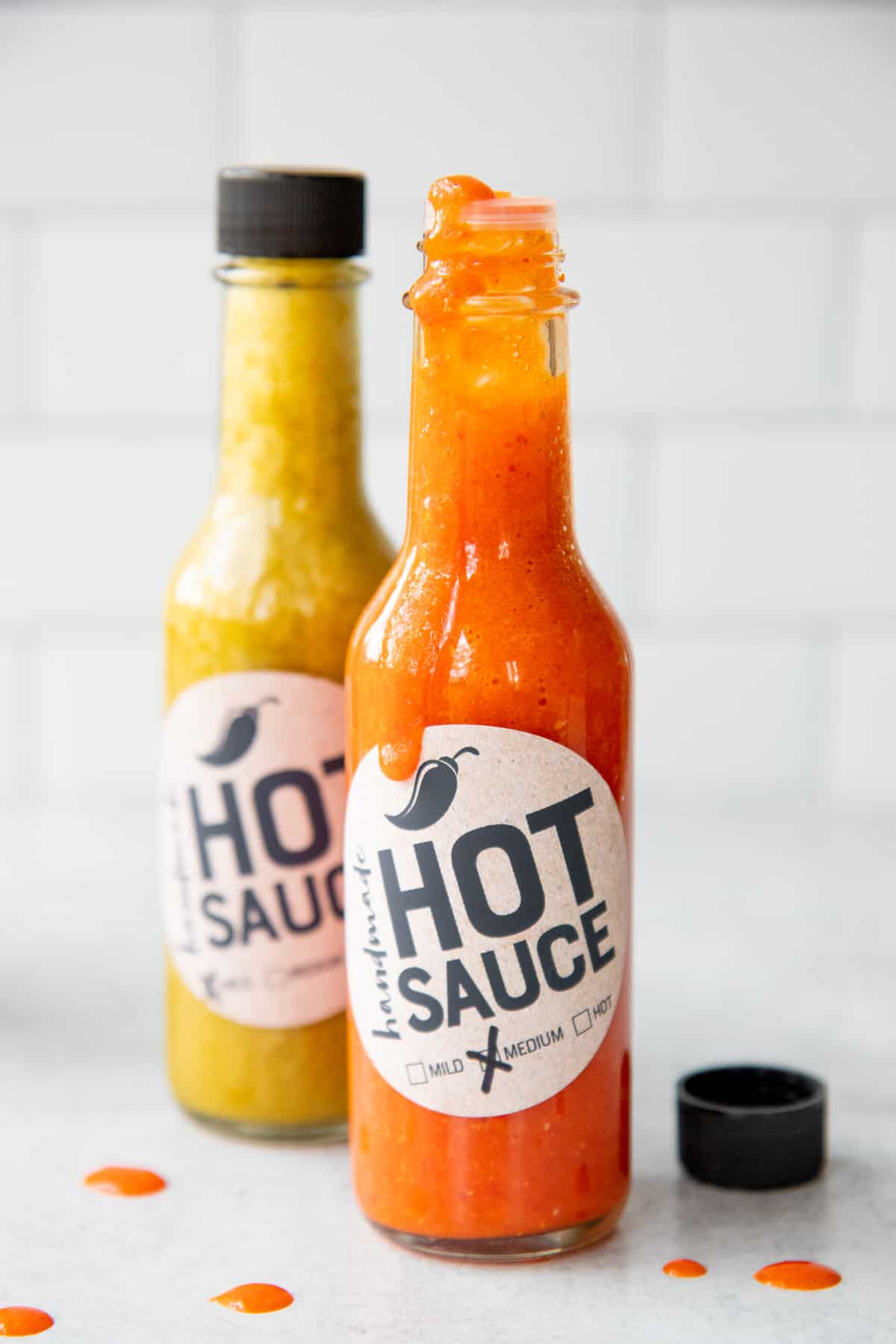 Two bottles of labeled hot sauce sit on a counter. One of the bottles is open.