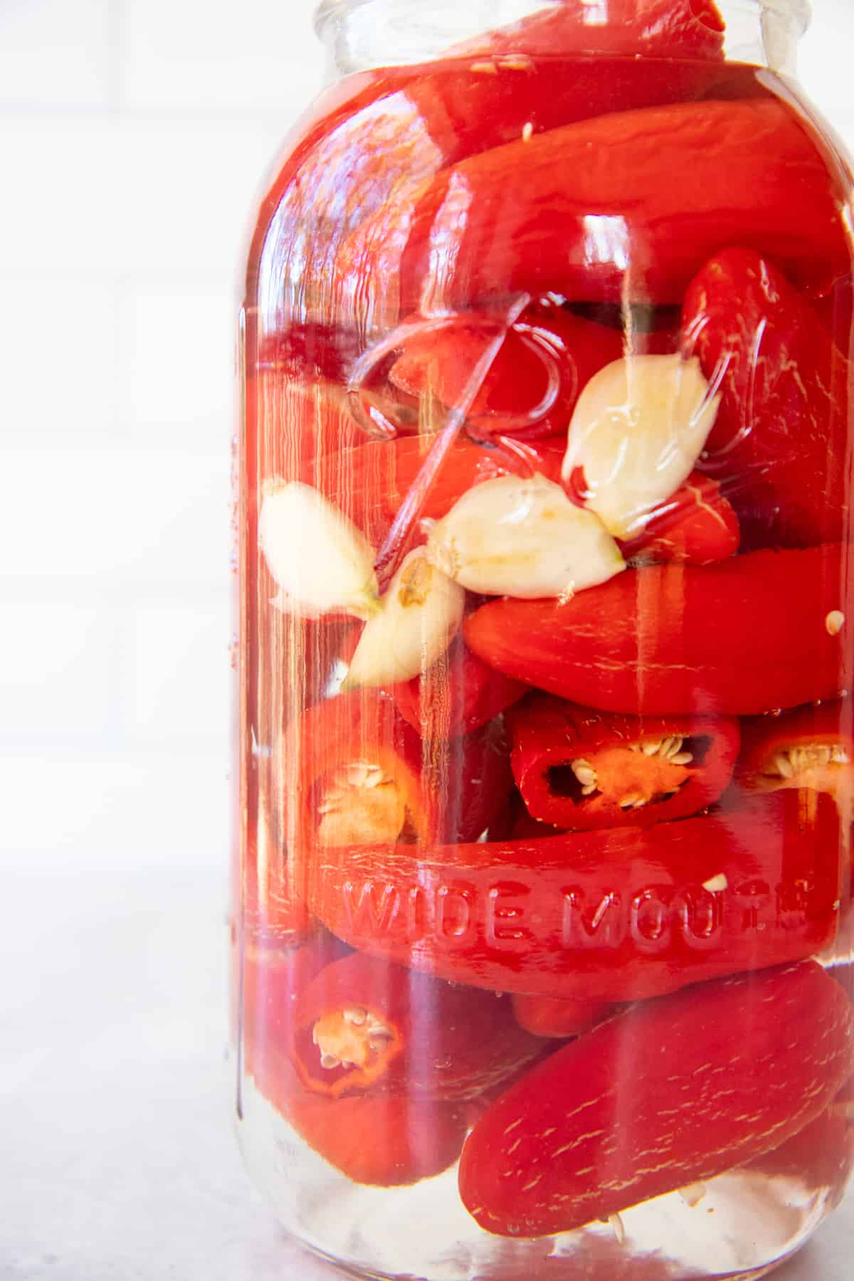 Close up of red peppers and garlic fermenting in a glass jar.