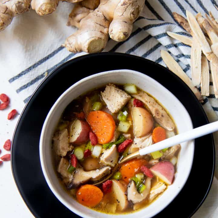 A spoon with a white handle sits in a white bowl full of herbal chicken soup. A knob of ginger is behind the bowl.