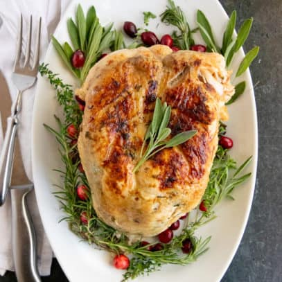 Cooked Instant Pot turkey breast on a bed of herbs and cranberries on a white platter.