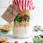 A mason jar filled with even layers of dry ingredients for cookie mix in a jar, topped with fabric, a baking instructions tag, and baker's twine.