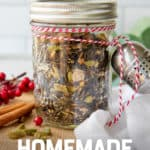 """A glass jar filled with loose leaf is tied to a tea ball with baker's twine. The jar is surrounded by spices. A text overlay reads """"Easy Holiday Gift! Homemade Chai Gift Set."""""""