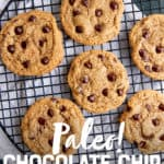 "Six almond flour chocolate chip cookies sit on a round wire rack to cool. A text overlay reads ""Paleo! Chocolate Chip Cookies."""