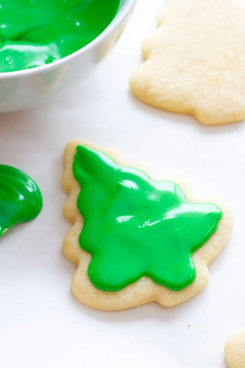 A tree-shaped cookie spread with green sugar cookie icing sits next to a bowl of frosting.