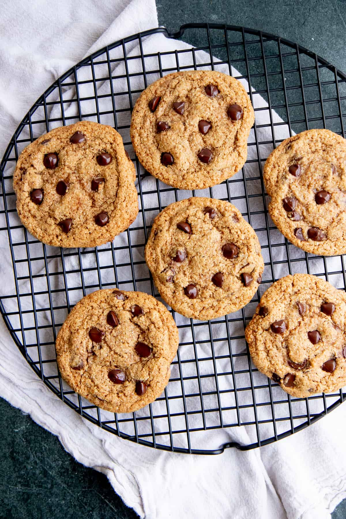 Six chocolate chip cookies sit on a round wire cooling rack.