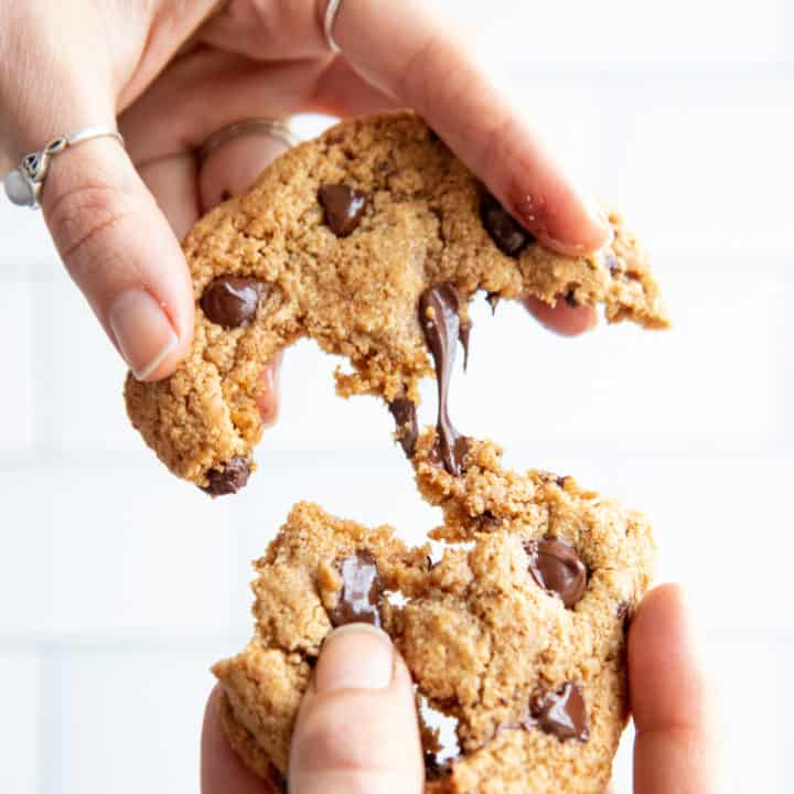 Two hands pull an almond flour chocolate chip cookie apart. Gooey chocolate stretches between the two cookie halves.