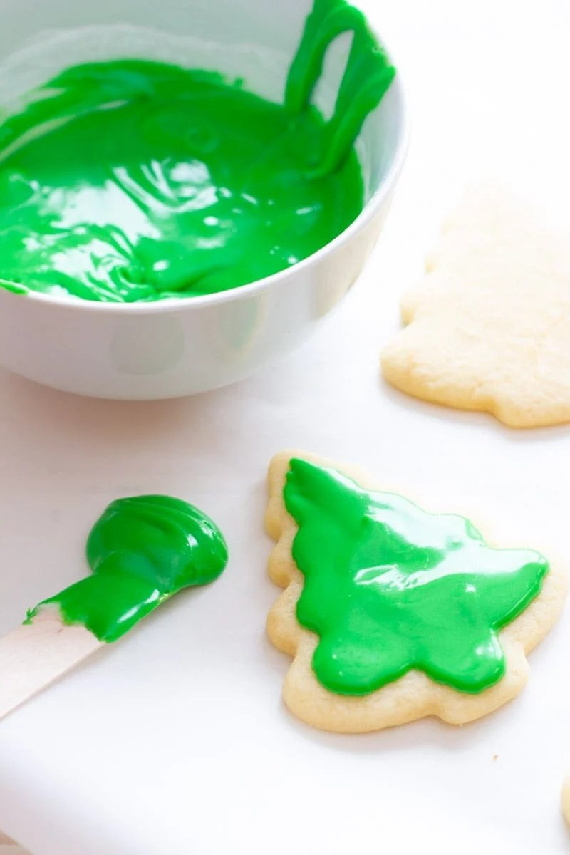 A tree-shaped cookie gets spread with sugar cookie icing.
