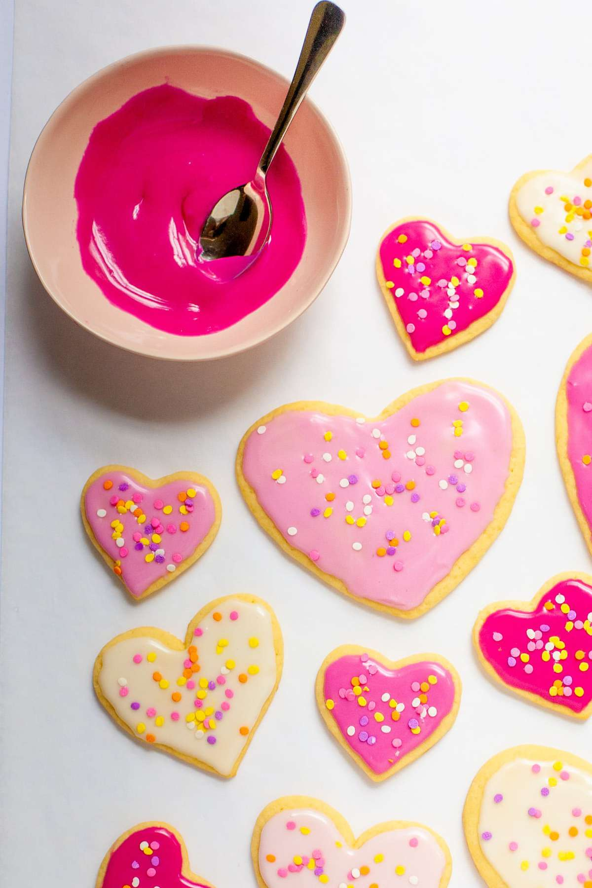 A pink bowl of sugar cookie icing sits next to heart-shaped cookies.
