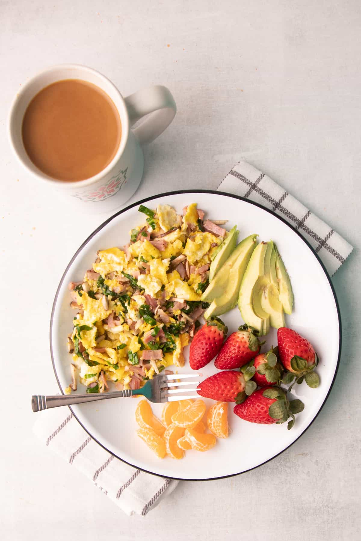 Breakfast on a white plate: egg scramble, fruit, and avocado. A mug sits next to the plate.