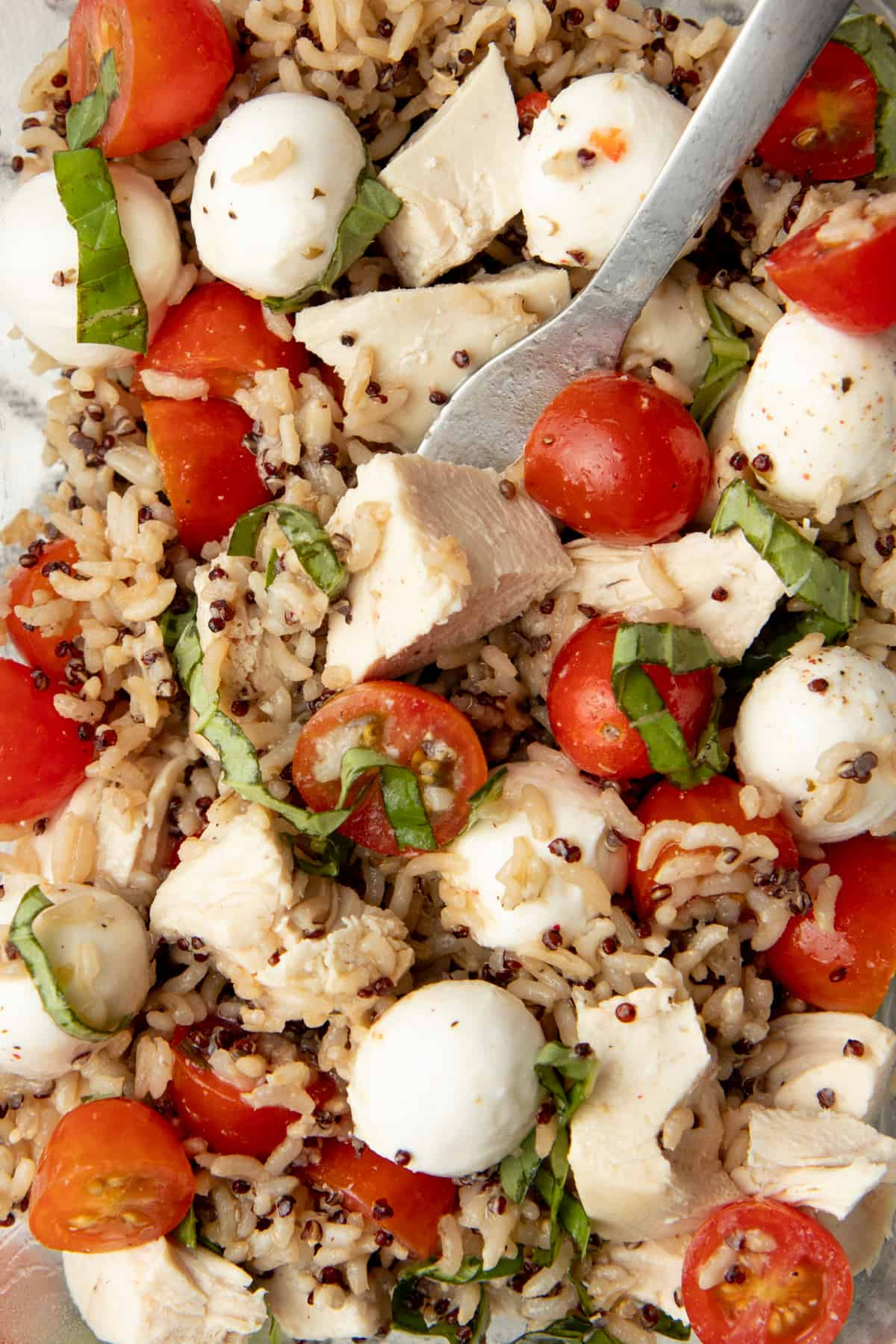 A fork rests in a caprese chicken grain bowl.