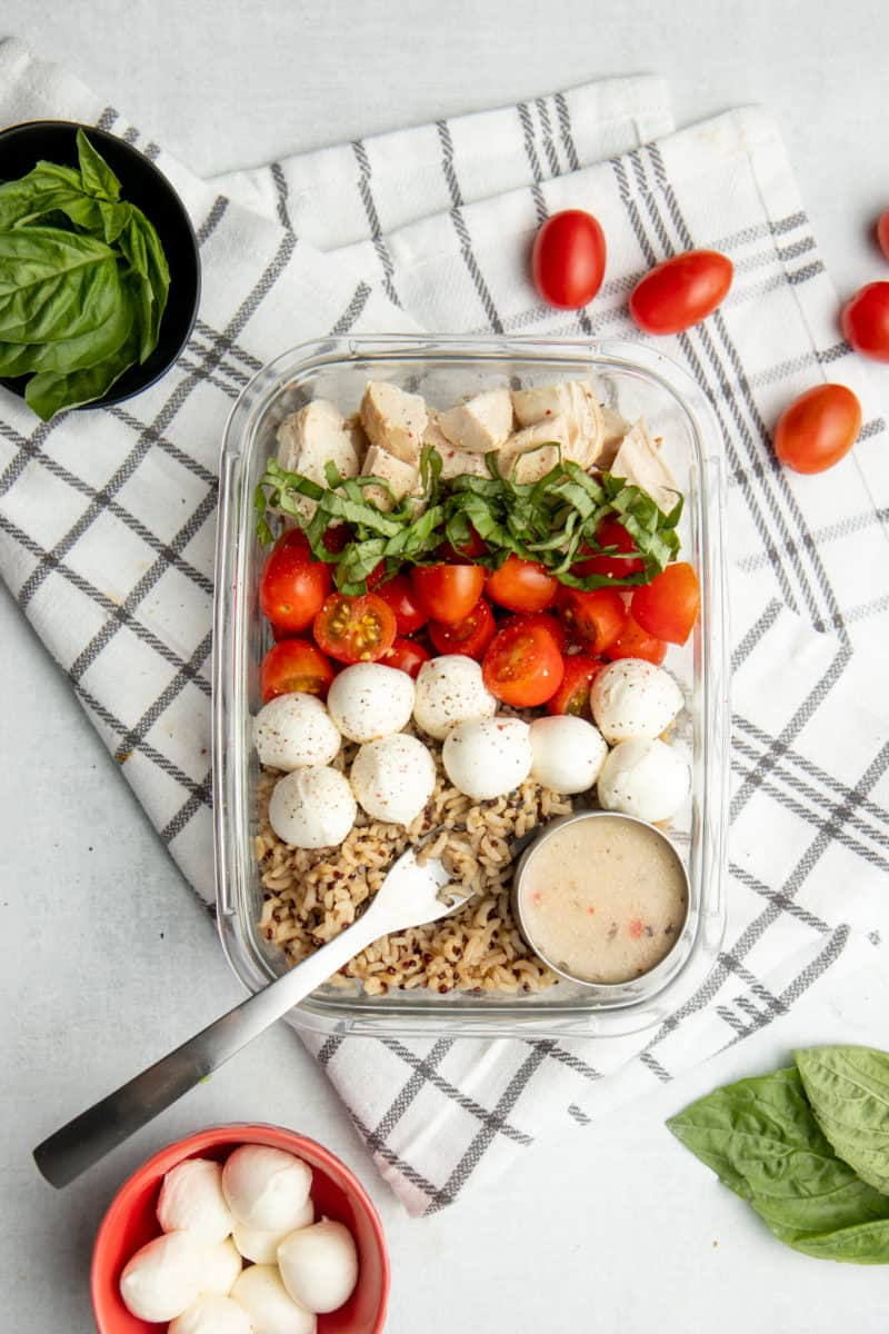A glass dish filled with grain bowl ingredients sits on a brown and white dishtowel. Tomatoes and mozzarella sit on the side.
