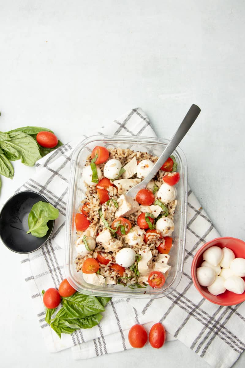 Tomatoes, mozzarella balls, basil, and grains are combined in a rectangular glass container. Container and ingredients sit on a brown and white plaid dishtowel.